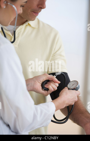 USA, New Jersey, Jersey City, Doctor checking patient's blood pressure - Stock Photo
