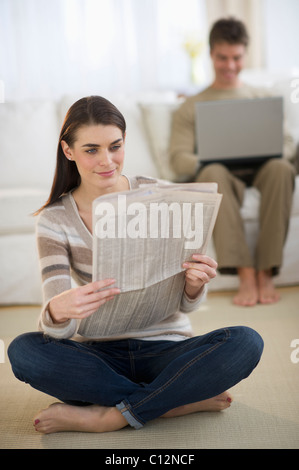 USA, New Jersey, Jersey City, Young woman reading newspaper while man is using laptop in background - Stock Photo