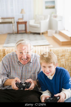 USA, New Jersey, Jersey City, grandfather and grandson (8-9) playing video games - Stock Photo