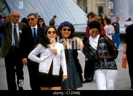 3 three young adult women, tourists visitors visiting, courtyard, Cour Napoleon, Louvre Museum, city of Paris, Paris, - Stock Photo