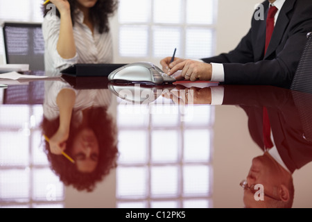 caucasian businessman and businesswoman in office meeting room, dialing on phone. Horizontal shape, side view - Stock Photo