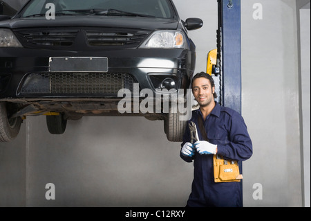 Auto mechanic working on a car wheel in a garage - Stock Photo