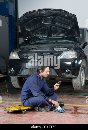 Auto mechanic using a mobile phone in a garage - Stock Photo