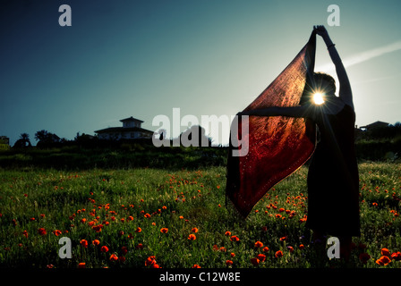 Woman holds red shawl in field of wildflowers, sunset, Granada, Andalusia - Stock Photo