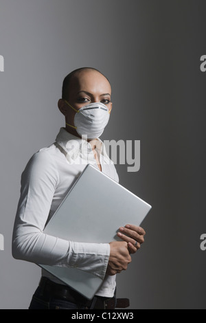 Gay man holding a laptop and wearing a flu mask - Stock Photo