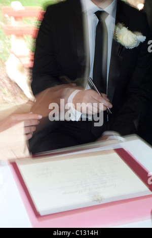 Groom signing marriage certificate guided by the bride - Stock Photo