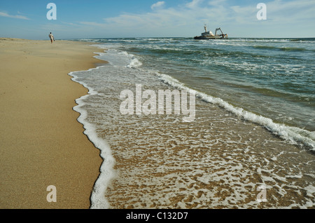 Seascape of lone man walking on desolate beach with ship wreck in background near Swakopmund Namibia Landscapes - Stock Photo