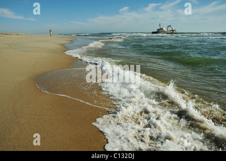 Atmospheric scene of man on deserted beach looking at stranded ship in water near Henties Bay Namibia Landscapes - Stock Photo