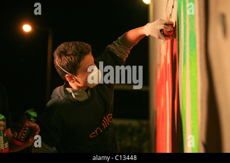 Young teens paint graffiti on a wall - Stock Photo