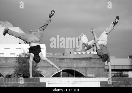 Two teenage boys practice free running - Stock Photo