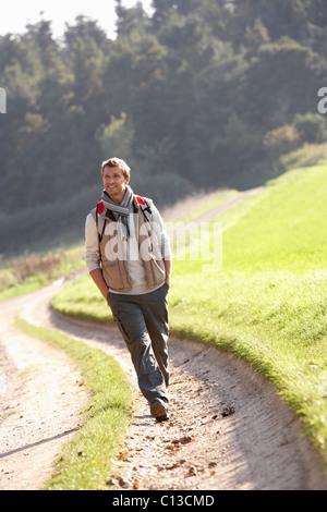 Young man walks in park - Stock Photo