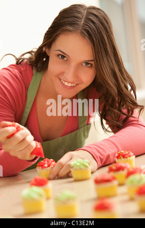 usa utah lehi portrait of young woman decorating cupcakes in kitchen stock - Woman Decorating Cupcakes