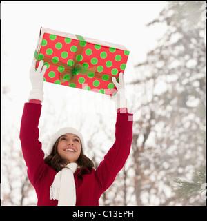 USA, Utah, Lehi, Young woman holding Christmas gift outdoors - Stock Photo