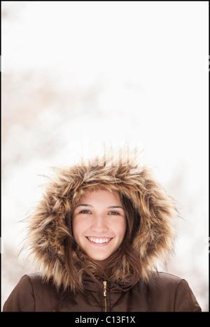 USA, Utah, Lehi, Portrait of young woman wearing fur hooded coat - Stock Photo