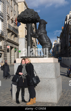 Tourist women posing in front of El Oso y el Madroño the Bear and Strawberry Tree sculpture at Puerta del Sol square - Stock Photo