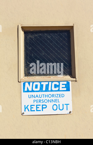 A sign posted on a door underneath a wire meshed window that reads: Notice Unauthorized Personnel Keep Out. - Stock Photo