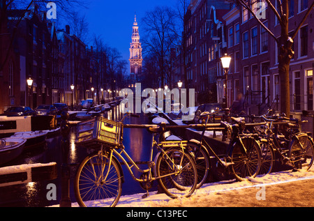 Netherlands, Amsterdam, Bicycles on bridge over canal - Stock Photo