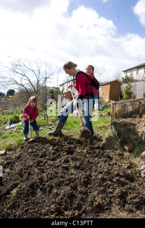 Woman with children digging allotment - Stock Photo