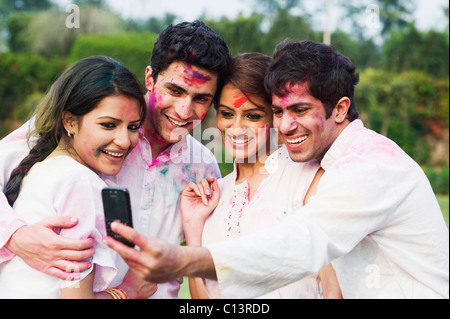 Friends taking a picture of themselves with a mobile phone on Holi - Stock Photo