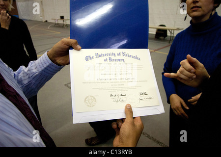 A man holds a college diploma for the University of Nebraska at Kearney. - Stock Photo
