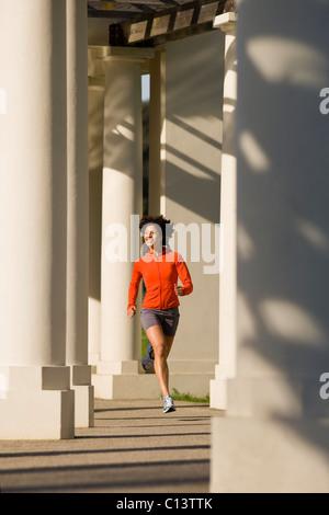 USA, California, Oakland, Young woman jogging - Stock Photo