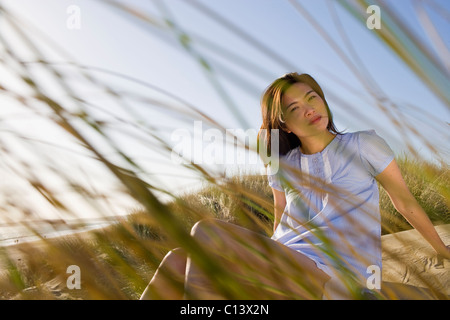 USA, California, Point Reyes, Young woman sitting in grass on sand dune - Stock Photo