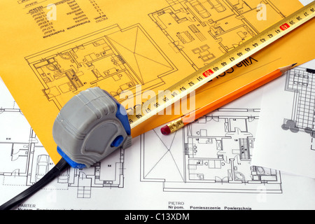 A measuring tape and a pencil on a floor plan blue print. Print on yellow and white paper sheet - Stock Photo