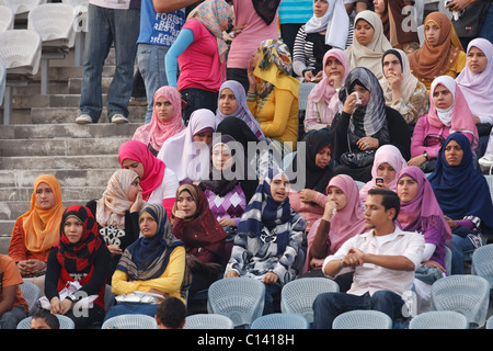 Young women spectators watch warmups prior to the 2009 FIFA U-20 World Cup soccer 3rd and 1st place matches in Cairo, - Stock Photo
