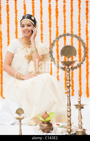 Bride in traditional South Indian dress talking on a mobile phone - Stock Photo