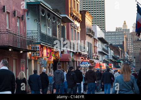 People cruising along bars and nightclubs on Bourbon Street at night in New Orleans - Stock Photo