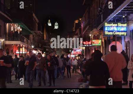 People drinking and walking along Bourbon Street in New Orleans with neon signs - Stock Photo