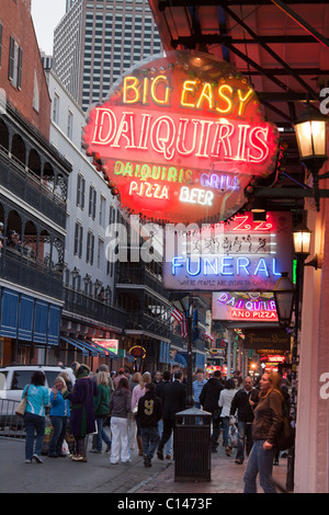 People walking by neon signs for bars and clubs along Bourbon Street in New Orleans at night - Stock Photo