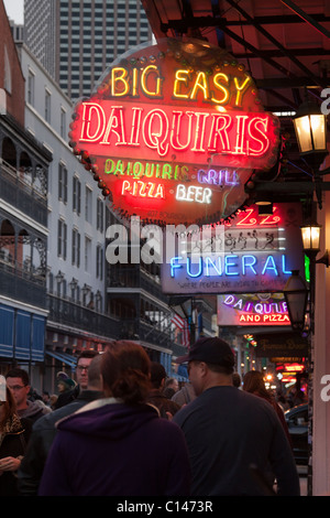 People walking below neon signs for bars and clubs along Bourbon Street in New Orleans at night - Stock Photo