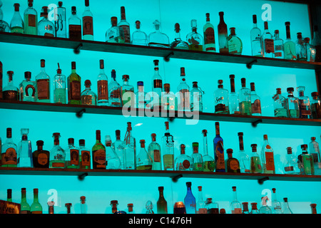 Slick display of glass liquor bottles on shelves with a bright blue glowing background in a bar - Stock Photo