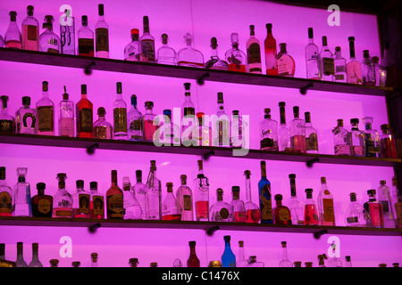 Slick display of glass liquor bottles on shelves with a bright purple glowing background in a bar - Stock Photo