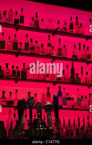 Slick display of glass liquor bottles on shelves with a bright red glowing background in a bar - Stock Photo