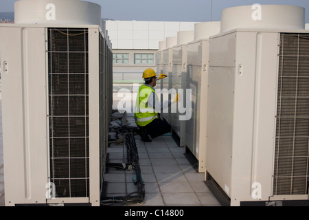 AC Tech repairing ac on roof - Stock Photo