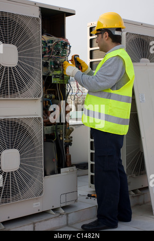 AC Tech repairing ac on roof - Stock Photo