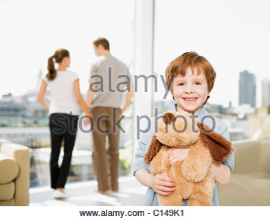 Boy holding stuffed dog with parents in background - Stock Photo