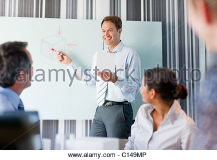 Businessman holding cube talking to co-workers in conference room - Stock Photo