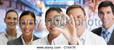 Business people looking at cog together - Stock Photo