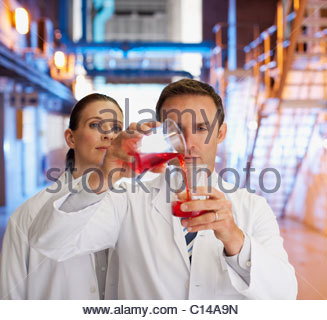 Scientists measuring liquids into beakers - Stock Photo