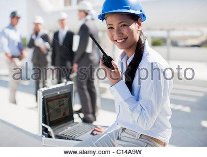 Businesswoman in hard-hat talking on walkie-talkie outdoors - Stock Photo