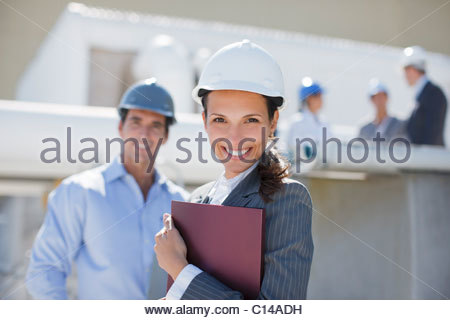 Businesswoman in hard-hat holding binder outdoors - Stock Photo