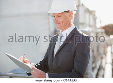 Businessman in hard-hat writing on clipboard outdoors - Stock Photo