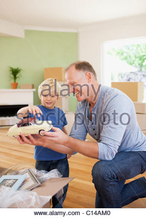 Father showing son model car in new house - Stock Photo