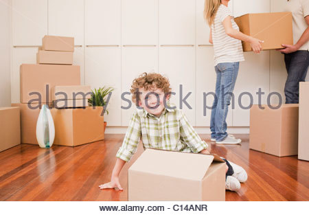 Boy sitting with box on the floor of his new house - Stock Photo