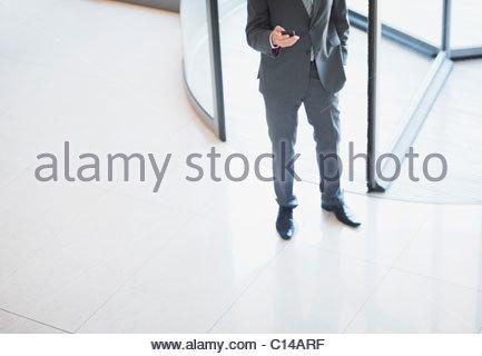 Businessman holding cell phone near revolving doors - Stock Photo