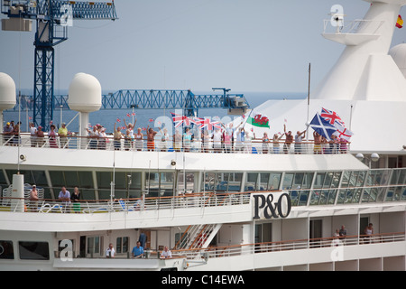 Passengers on board 'Artemis' waving flags as P&O ship sails passed in Barcelona Harbour. Spain - Stock Photo