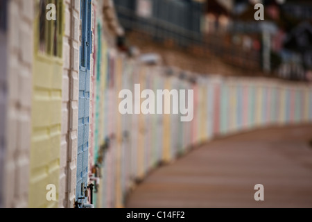 A row of colourful beach huts on the promenade at Lyme Regis in Dorset. - Stock Photo